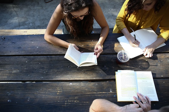 Image of friends writing in notebooks