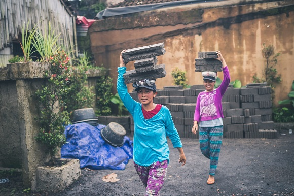 Two women balancing concrete blocks on their heads