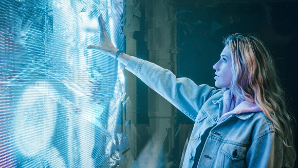 A woman reaching out to a large electronic screen