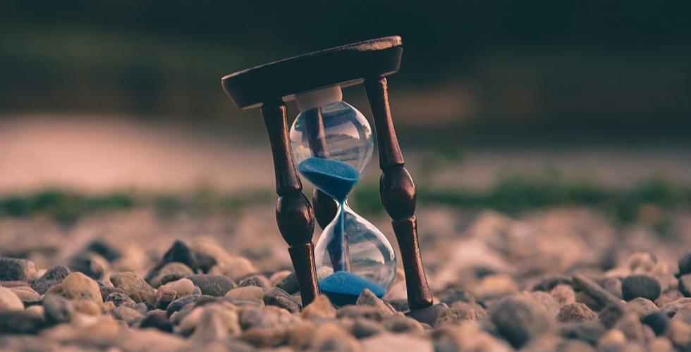 Image of hourglass amongst pebbles