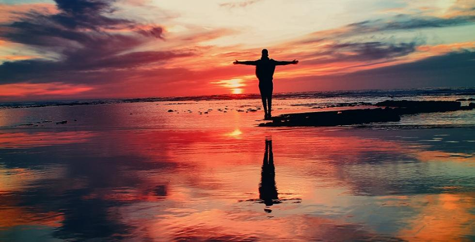 Image of person standing in front of a sunset