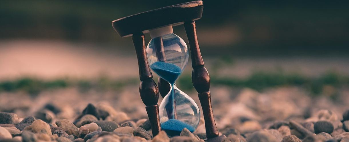 Image of hourglass amongst pebbles