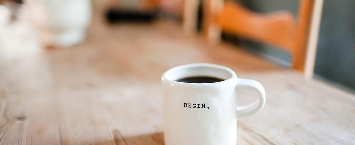 Coffee cup on a desk with the word 'Begin' on it.
