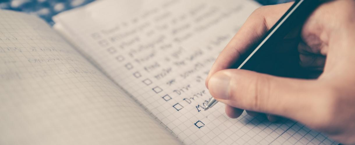 Image of person's hand writing a goal checklist