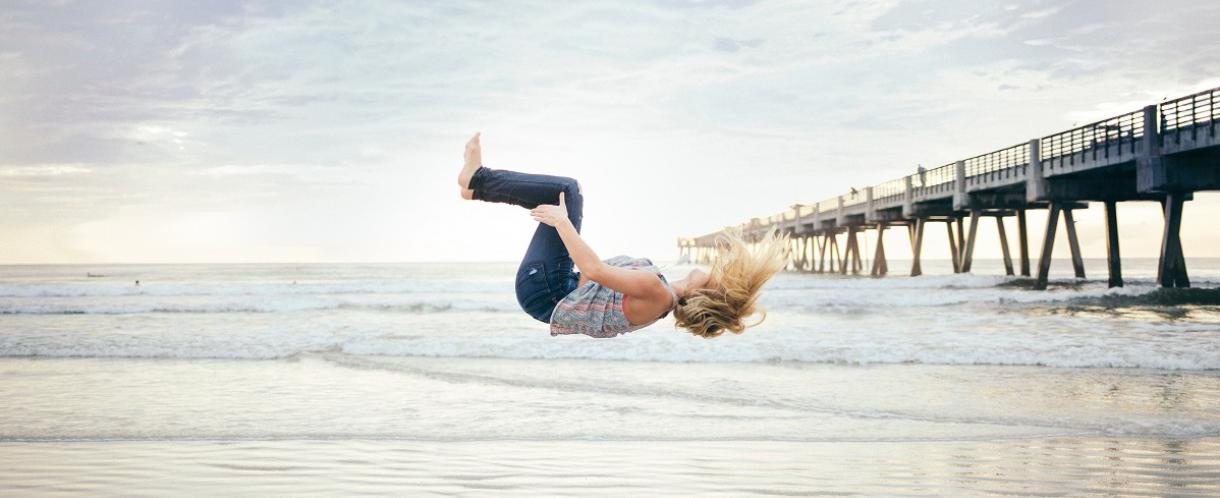 Image if woman mid-jump on a beach